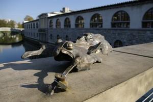 O broscuta din bronz sta la soare pe un pod - cu bratari din lacate
